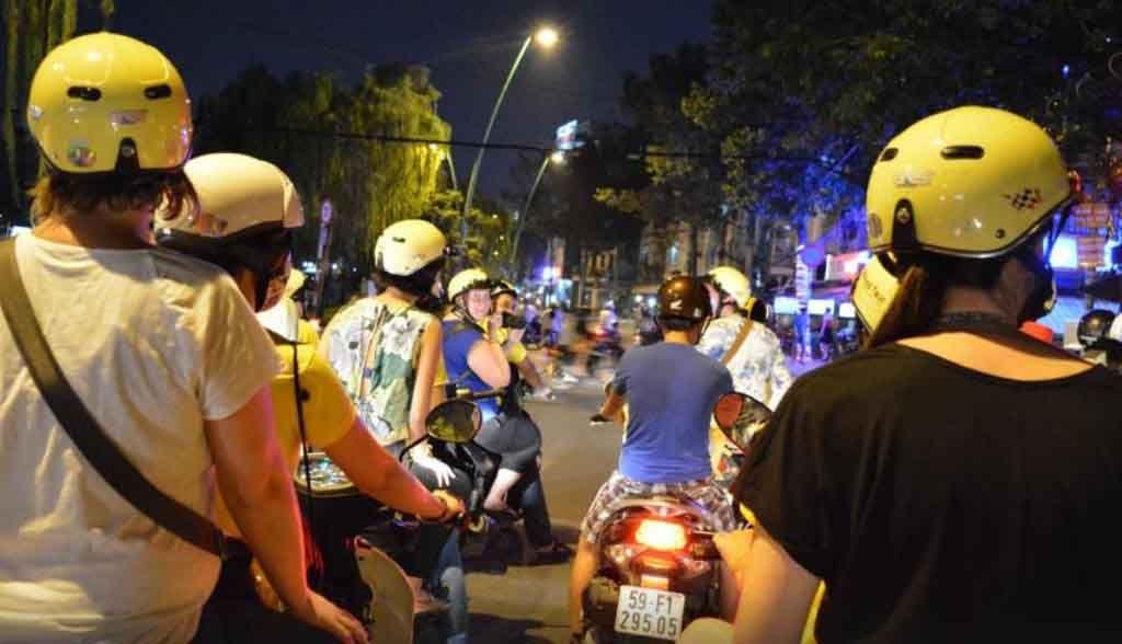 Vietnam Reisen - Sie fahren auf dem Rücksitz von Mopeds durch Saigon